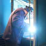 Man in welders booth, actively using welding equipment