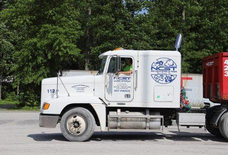 White semi truck against green tree background