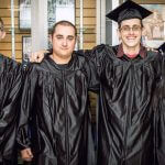 4 NCST graduates smiling while wearing the cap and gowns