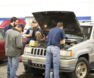 a group of ncst students working on a car in their shop