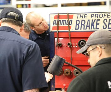 students looking at a brake system in shop