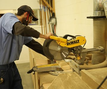 student using table saw to cut a piece of wood