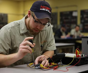 Electrician student with screwdriver in hand works on an open piece of technology