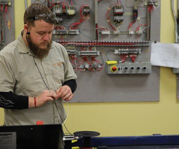 ONe electrician student stands working on wiring