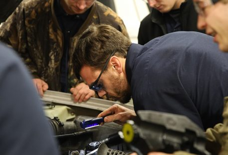 man bent over fixing car engine in shop