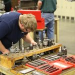STudent stands over various pieces of equipment for the CNC machine.