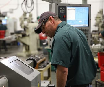 Instructor stands beside CNC machine computer, closely monitoring what is on the screen