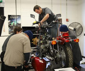 Three men work on a motorcycle that is on a table.