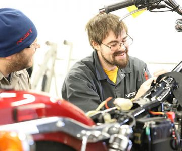 Man sits smiling while working on a motorcycle