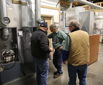 Three men stand around a Heating unit, going over the processes to fix it.