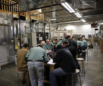 A large group of men in a factory setting sitting around tables