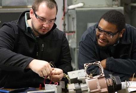 two trade school students working in the lab