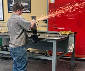 student welding with sparks flying from instrument hitting the metal