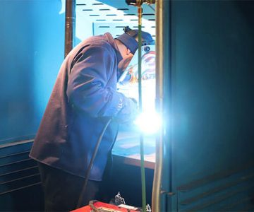 One man stands in a welding booth, working on welding project