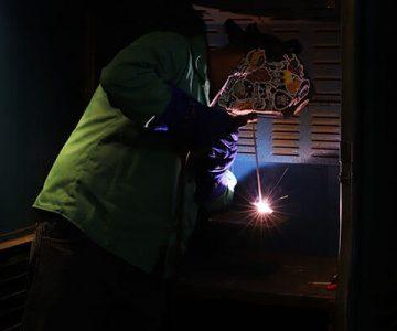 student welding using torch in dark lit room