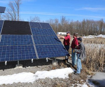 Three people stand to the right of a large solar pannel