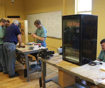 A classroom setting showing 5 men working on various parts of a refrigeration system