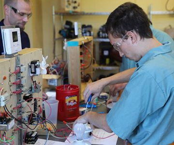 One HVAC student works on the wiring of a heating control system