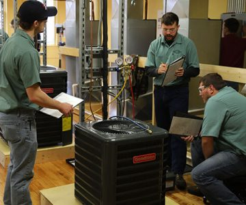 Group of three men work on an air conditioning unit