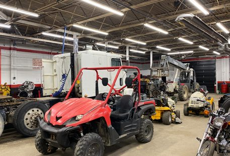 atv, lawnmower, other small engine vehicles sitting in shop