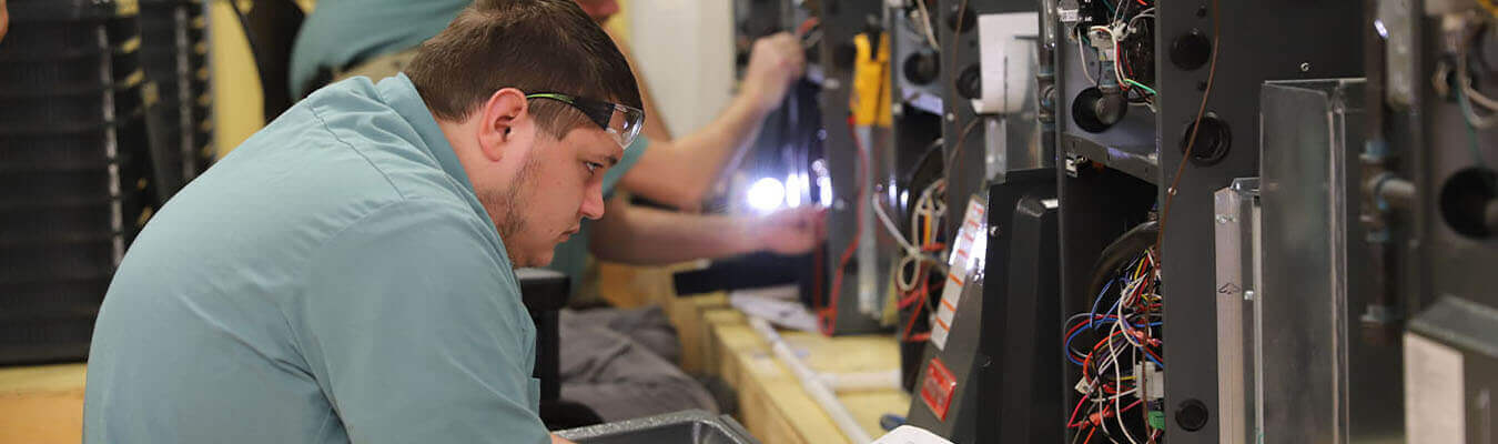 refrigeration and climate control student looking inside an HVAC unit