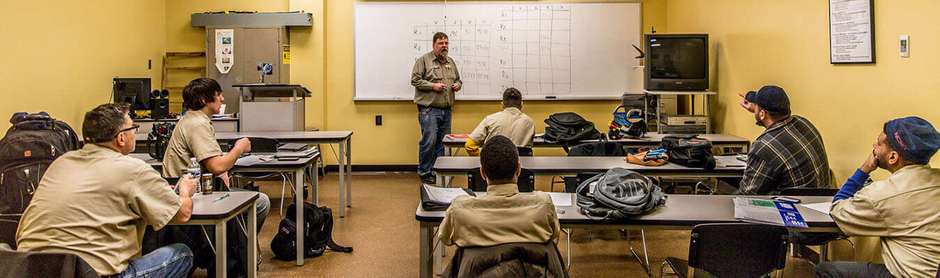 classroom shoot at the New Castle Campus with instructor teaching students in uniforms
