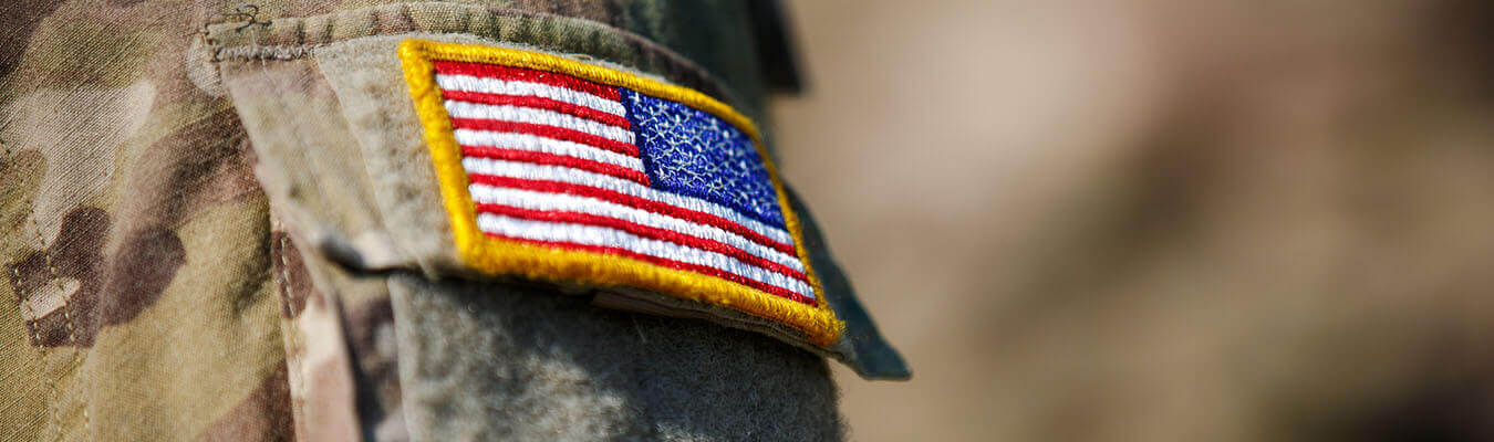 up close image of a military individual in uniform with the american flag
