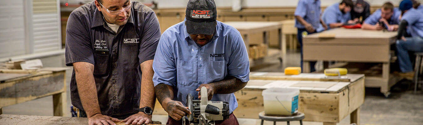 student and instructor working in the building technology lab at NCST cutting wood