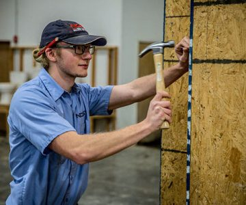 ncst building trades student hammering against wall