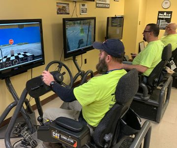 3 ncst students practicing their driving on a computer simulator