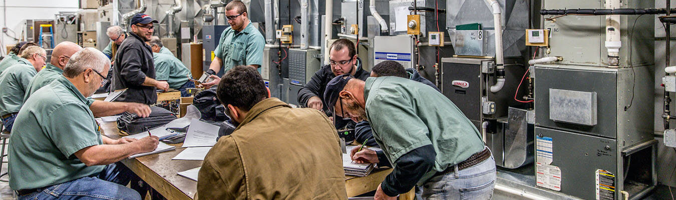 NCST students working at table inside the HVAC lab at the New Castle Campus