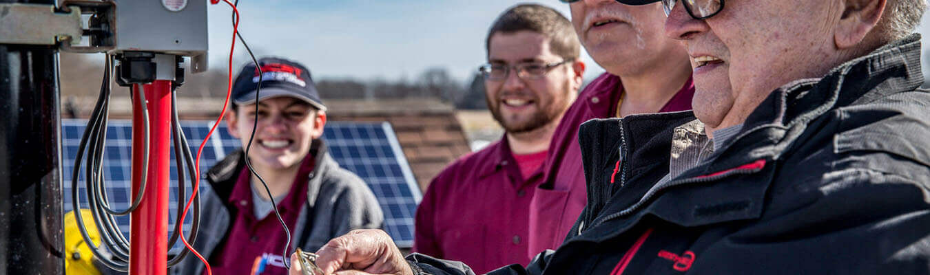three students watching NCST instructor work on outside solar panel