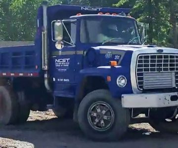 blue NCST dump truck on yard
