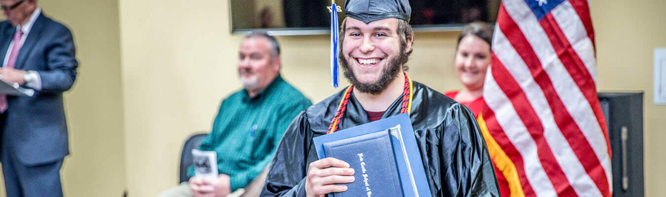new castle school of trades student who just graduated wearing his cap and gown with diploma