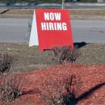 now hiring sign sitting by road outside business