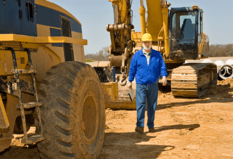Heavy Equipment With Operator walking next to it